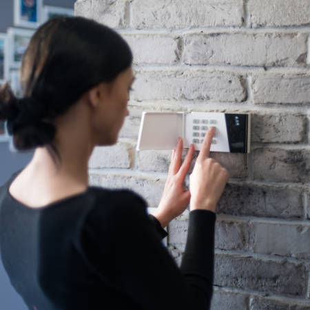 woman setting a burglar alarm to secure her property