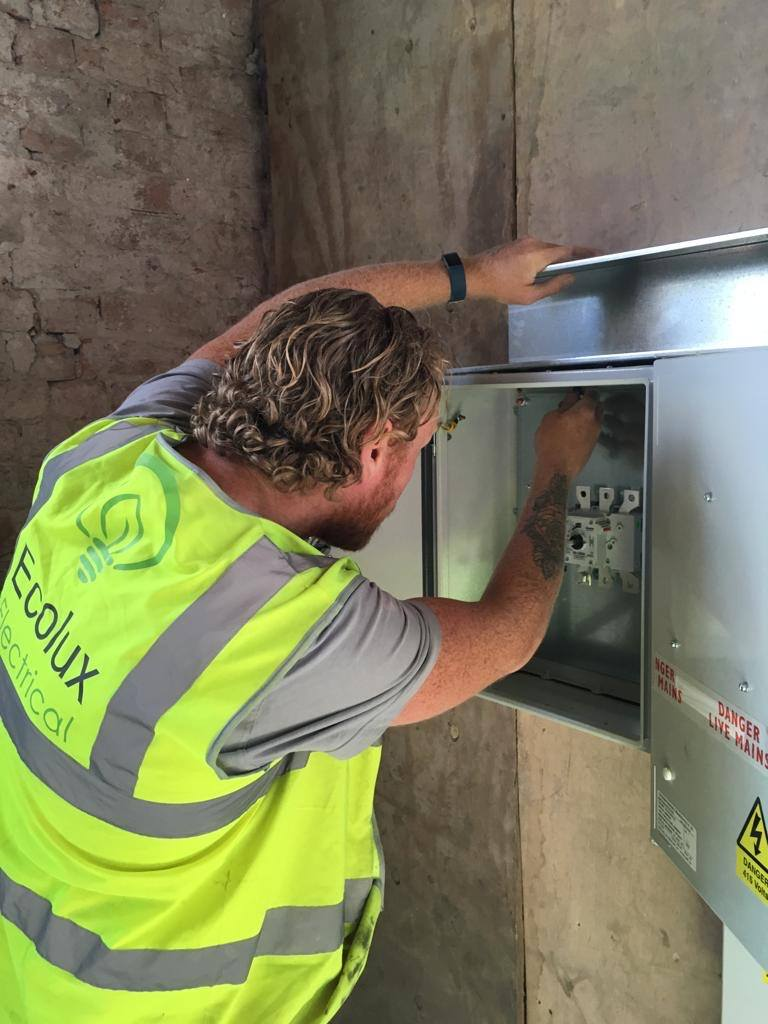 A qualified electrician installing a new distribution board in an industrial location