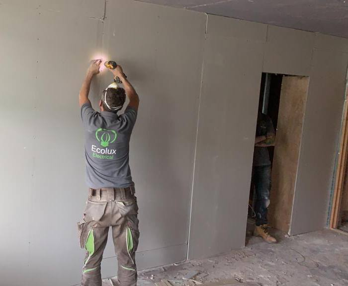 An electrician drilling fittings into a wall.